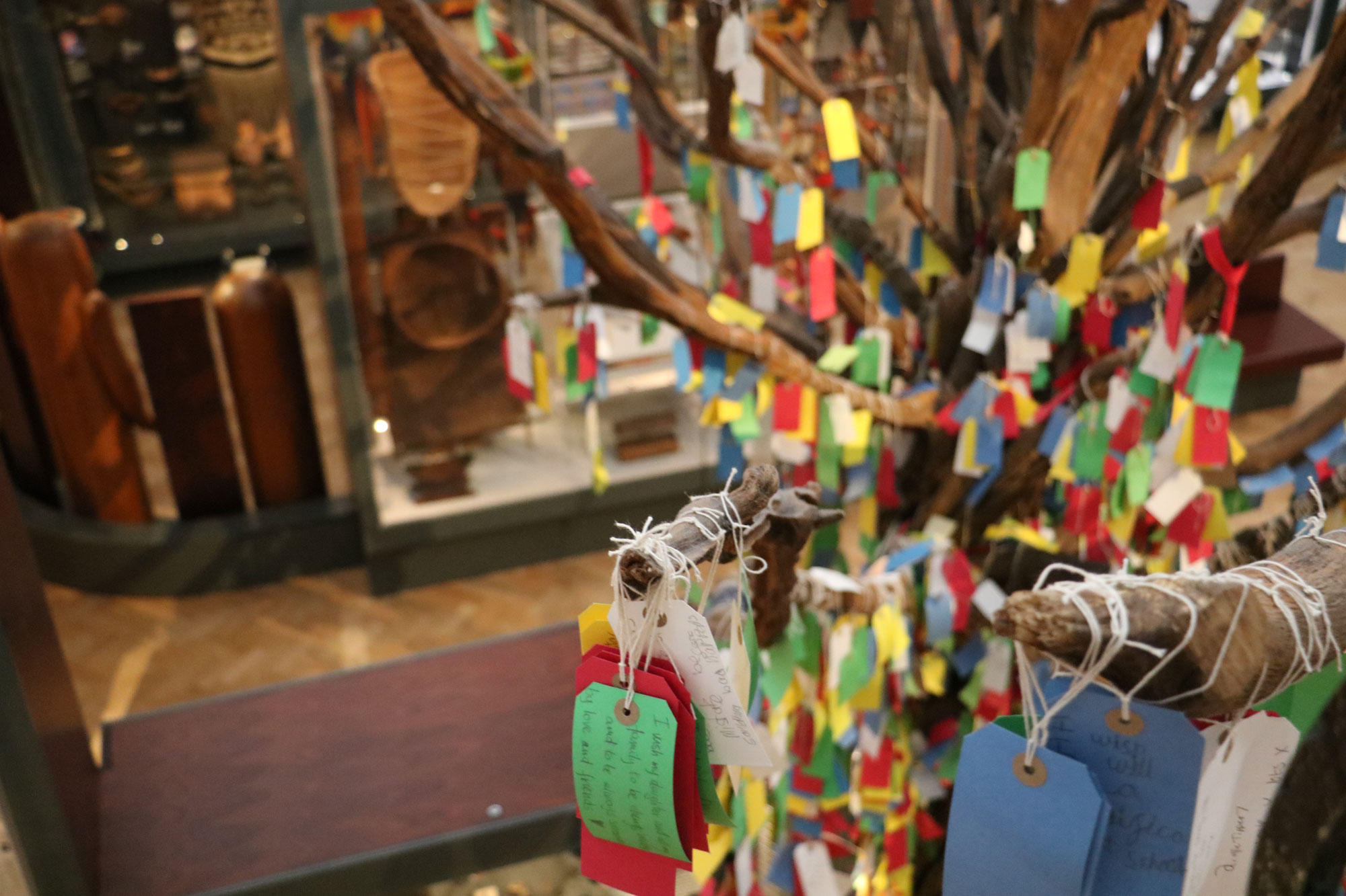 A fake tree in a gallery with many colourful labels hanging off of the branches by strings.