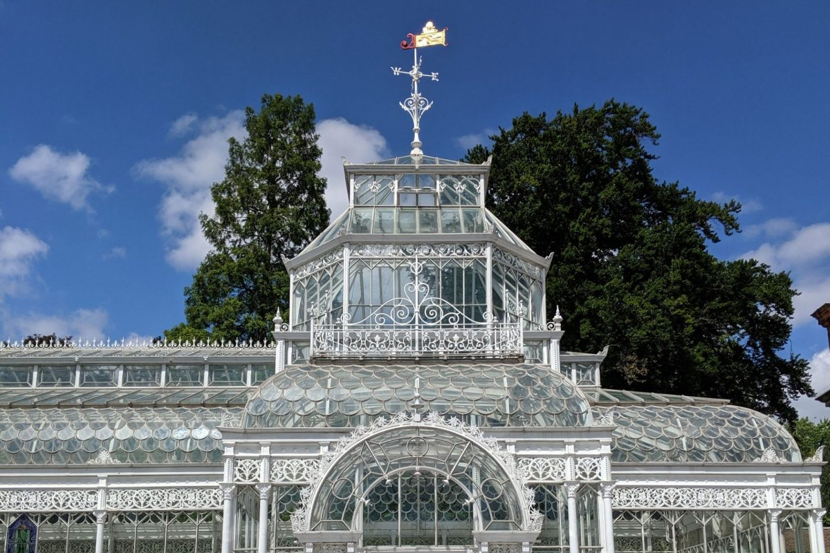 A partial view of an old white metal and glass conservatory seen on a sunny, blue sky day. The conservatory door is in front of us under an arch, with a small glass tower behind it and a weather vane on top. There are two bollards in front of the conservatory.
