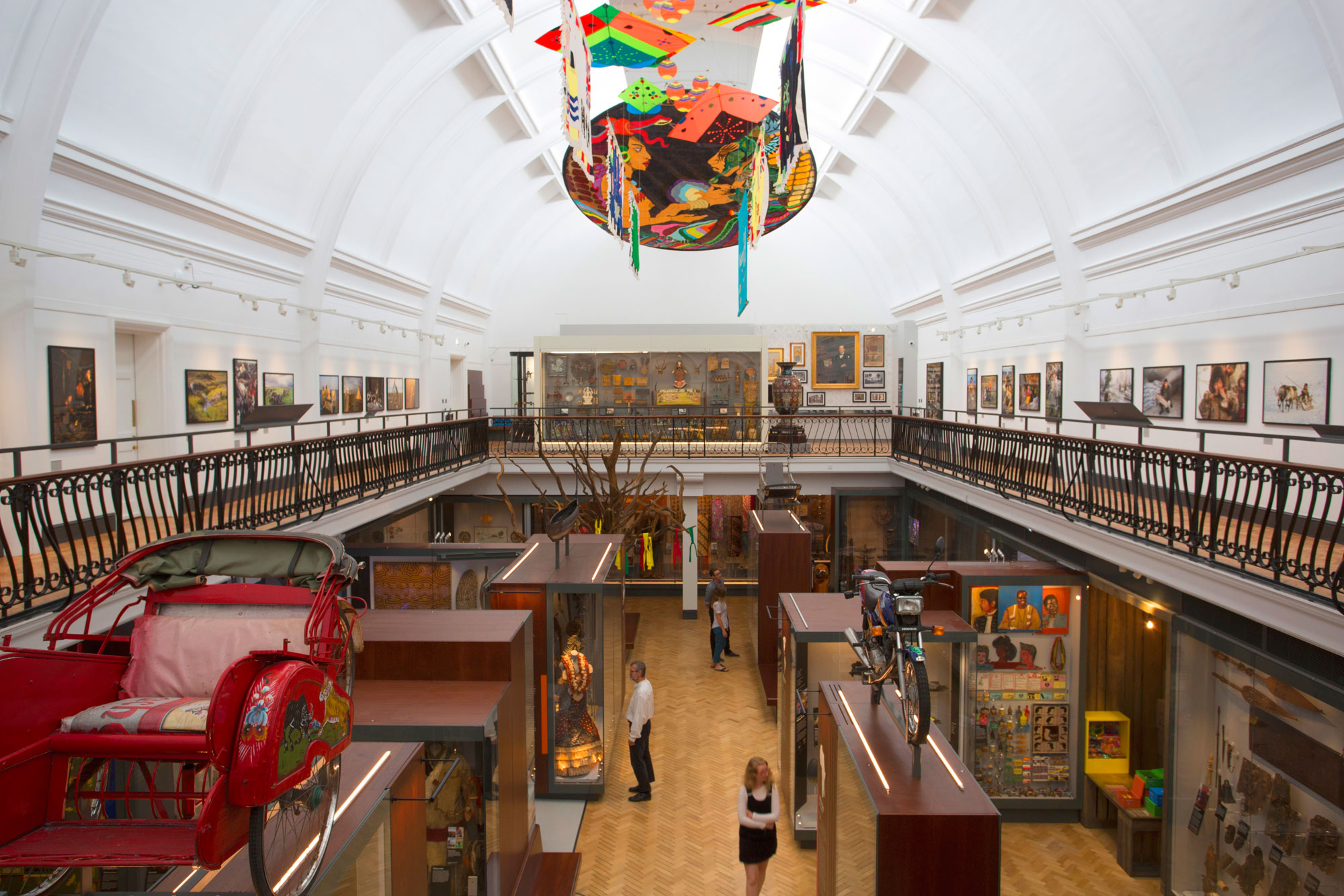 An aerial photograph of a gallery with a few people wondering through it below. There are cases full of objects and some large objects on the tops of cases, like a motorbike and a sled. There is a white domed ceiling and kites on the ceiling are visible.