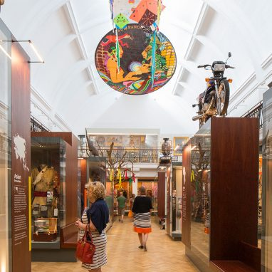 A photograph of a gallery with a few people wondering through it below. There are cases full of objects and some large objects on the tops of cases, like a motorbike and a sled. There is a white domed ceiling and kites on the ceiling are visible.