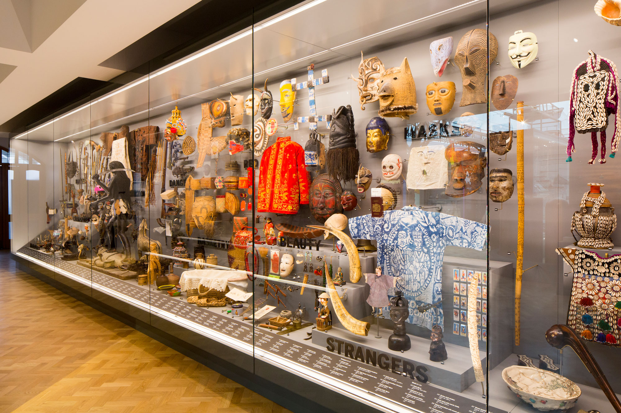 A glass case, seen diagonally, filled with objects grouped by category, like shells, masks, red things, strangers and danger.