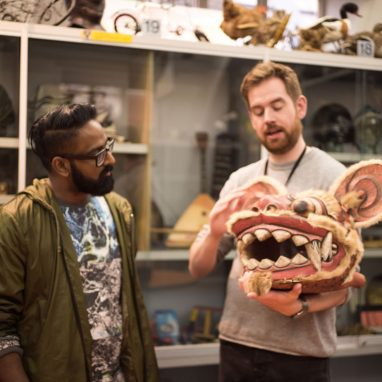 A man showing another man a head mask in the shape of a Chinese dragon. They are in a room full of objects on shelves behind them