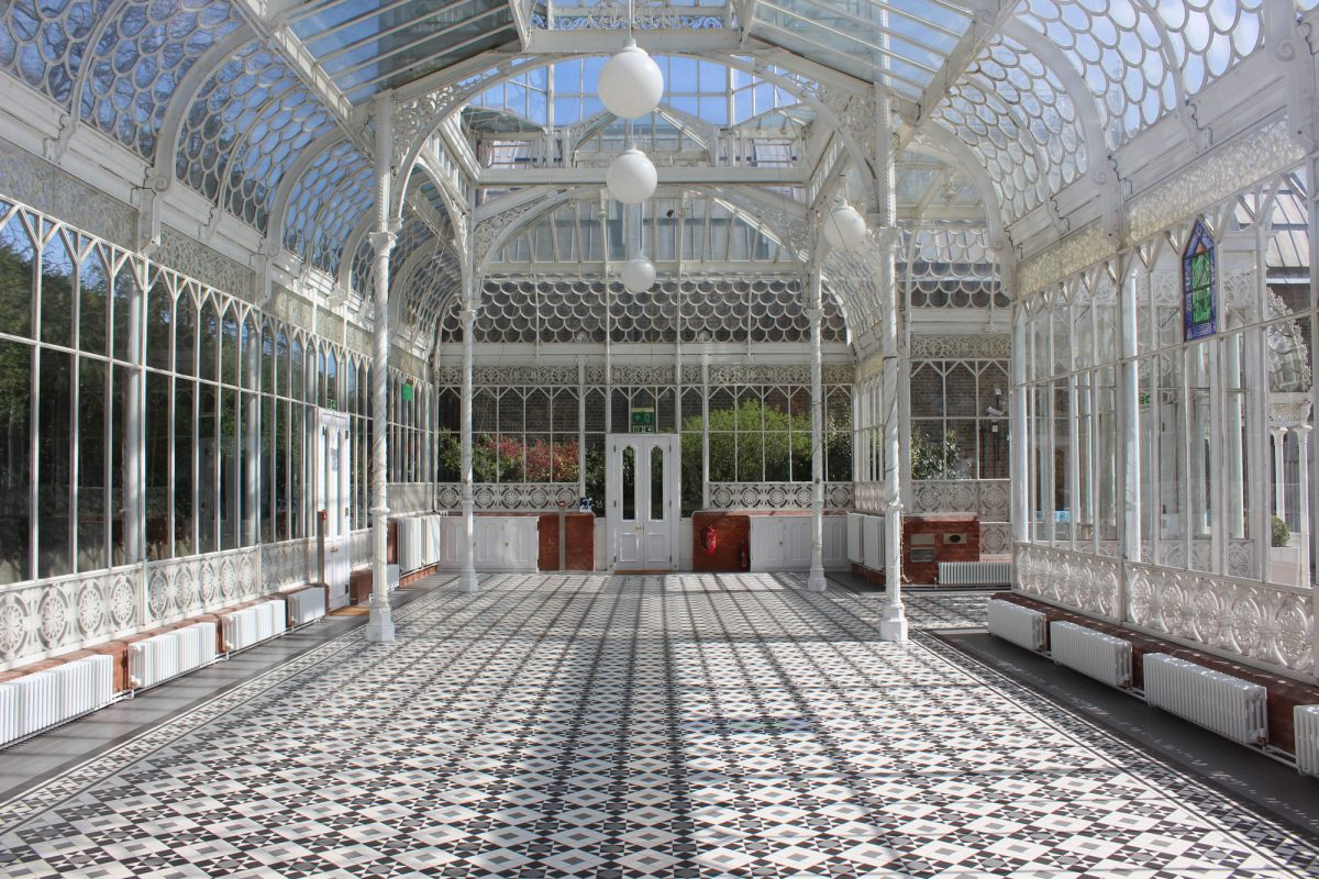 The inside of old old white metal and glass conservatory, with white metal poles around the edges. The floor is a pattern of black and white tiles. There are three globe shaped lamps hanging from the ceiling and there is a double white door at the end. short white radiators edge the space.