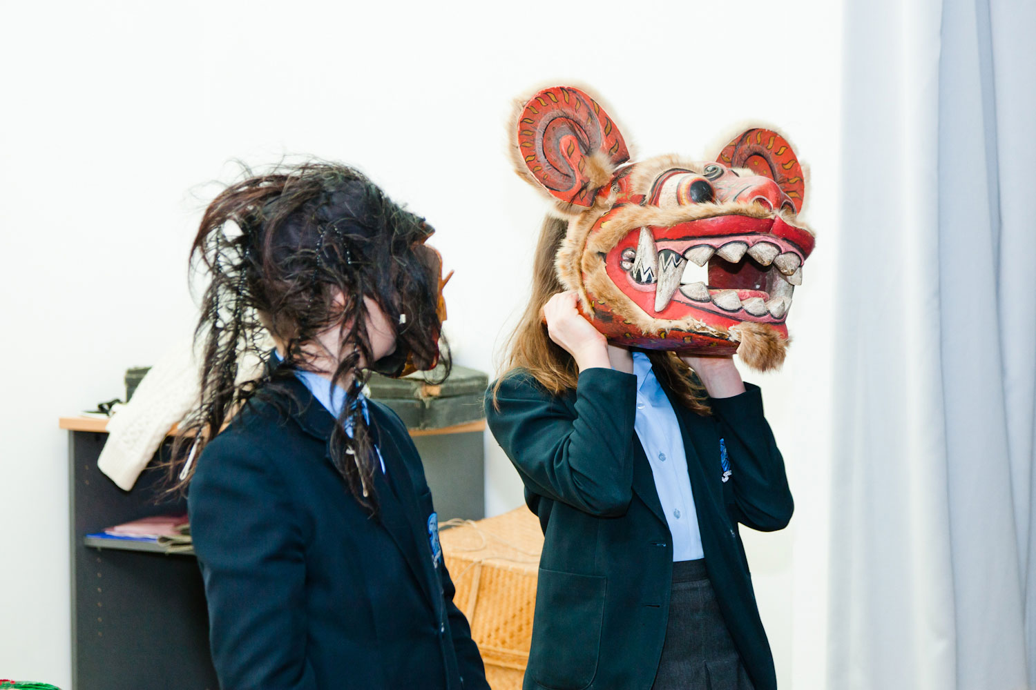 Two school children in blue uniforms have mask heads on. One is turned away from the camera, but the other is a large chinese dragon mask.