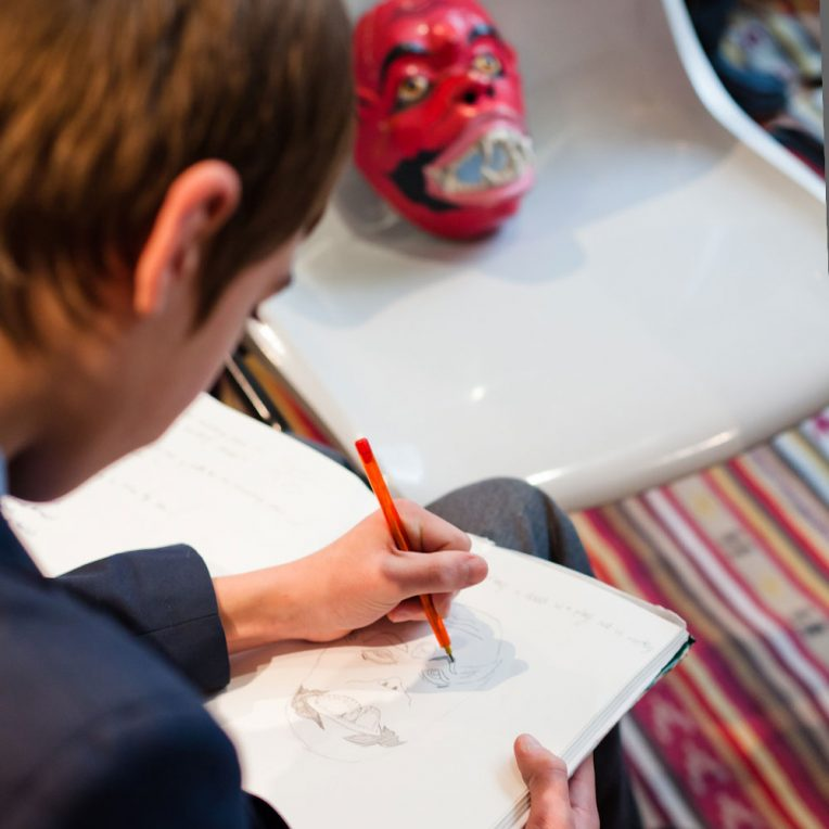 A boy in school uniform is drawing a red face mask propped up oin a grey plastic chair in front of him.