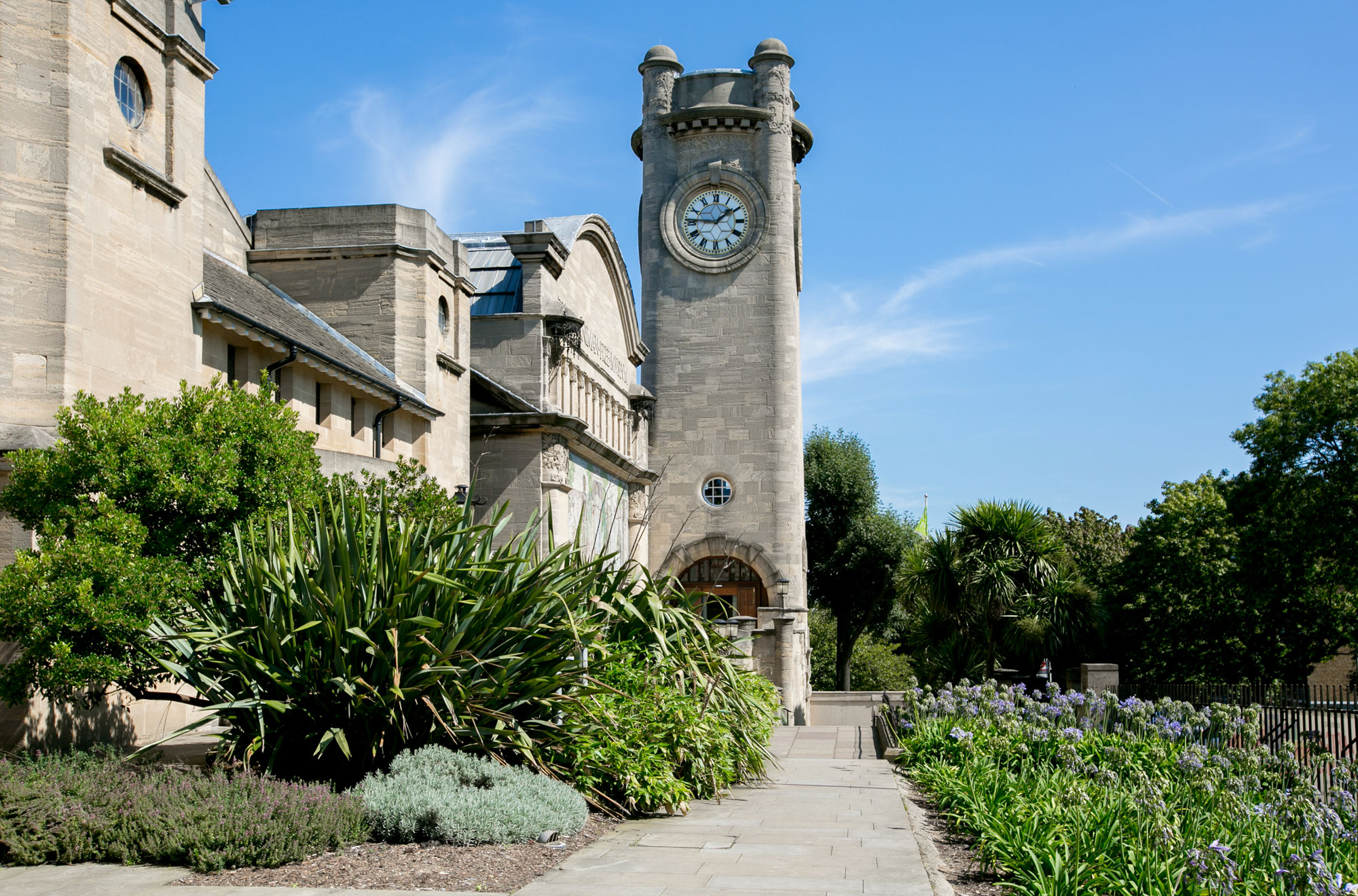 A tall square tower with rounded edges. It has four small rounded turrets at the top and a clockface near the top of the tower. There is a door (just seen) in the base. Buildings stretch out from the Clocktower towards the camera on the left, with small trees and shrubs in front. There is a flower bed on the right hand side and a path leading between them to the tower. The day is sunny and the sky is blue.
