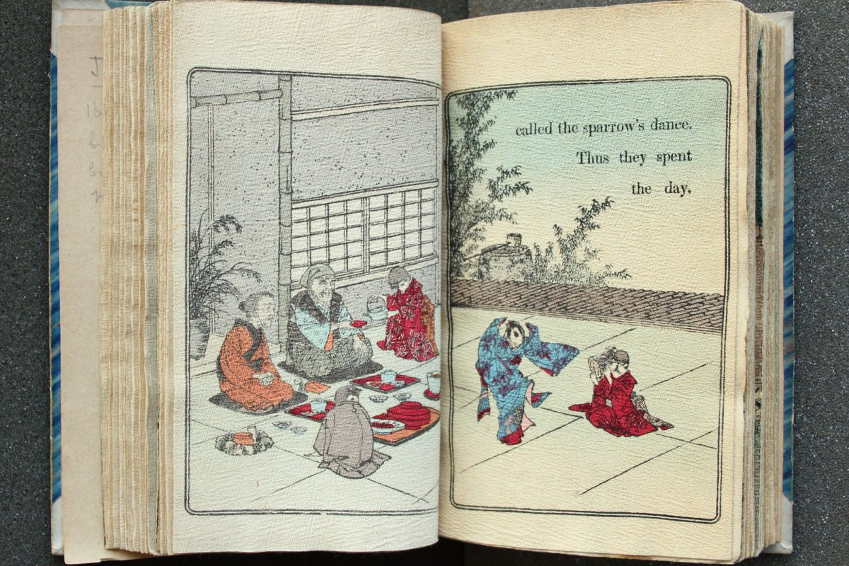 "An old book is open to a page showing a two page illustration of a group of people in Japanese dress sitting on the floor drinking tea next to a building. Two children are playing to one side and the words are written, ""Called the sparrow's dance. Thus they spent the day."""