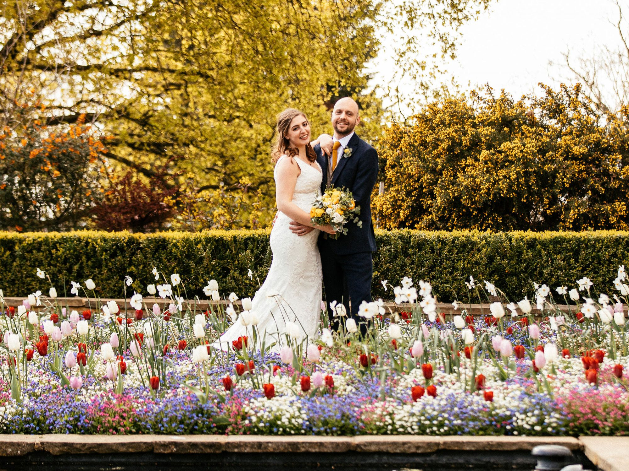 A bride and groom stand among white, red and blue flowers