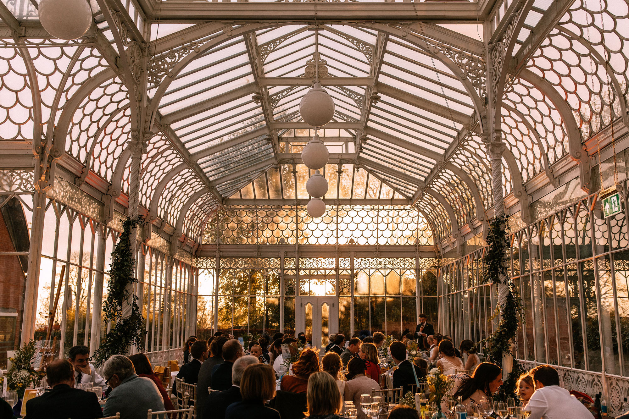 A group of people sitting down to dinner in a conservatory at dusk. The conservatory is filled with gentle orange light.