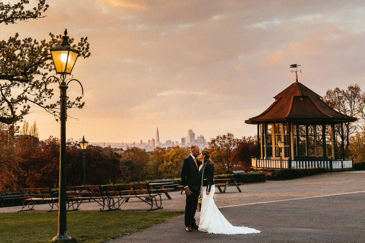 A bride and groom face each other in front of a vista of the London skyline at dusk. There is an old lamppost and tree to the left on a patch of grass, with a terrace stretching out behind them to a bandstand illuminated in the sun