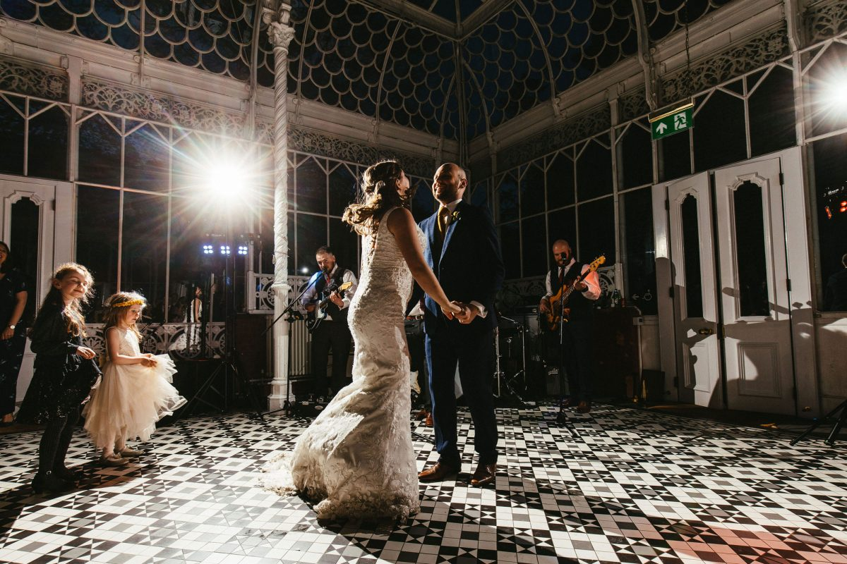 A bride and groom dance on a black and white tiled floor in a conservatory at night. The image is shot from below, and you can see movement in their figures. There are two children watching from the left and other adults watching from behind the couple.