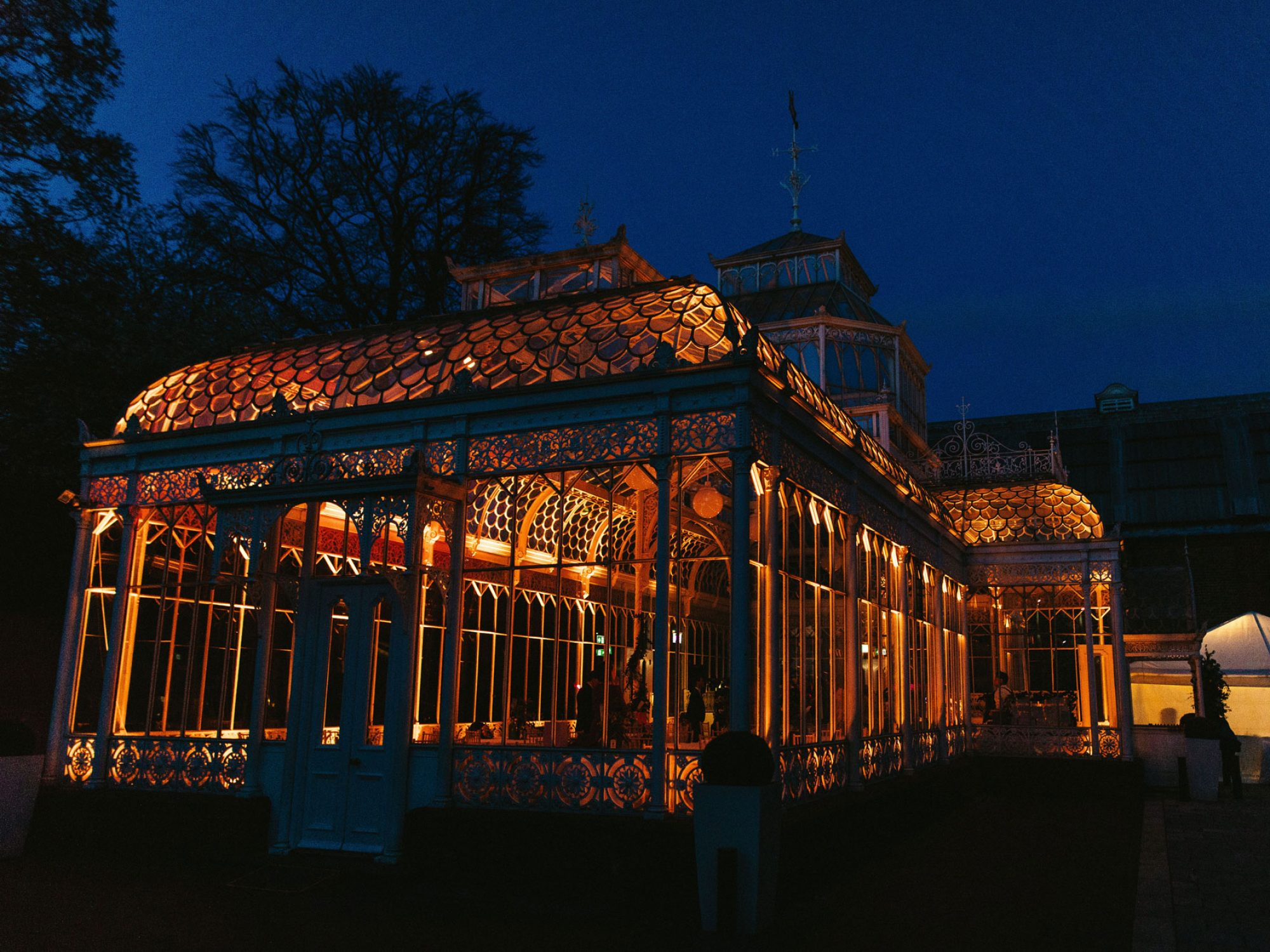 A conservatory lit up at night, as seen from outside