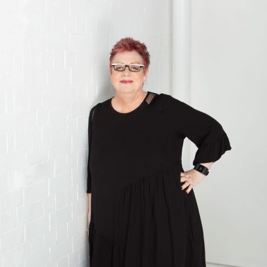 A woman in black leaning against a white brick wall