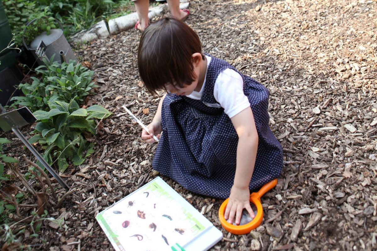 A very young girl crouches down with a pen in her hand, looking at a sheet with pictures on it. Next to her is a magnifying glass. She is on a wood chip strewn trail leading past a fence through trees.