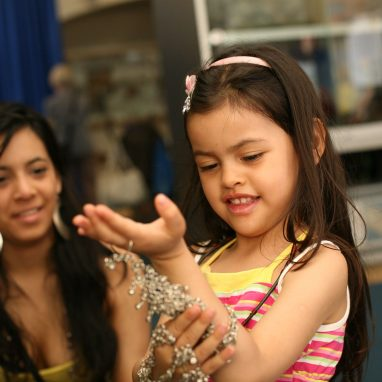 A girl is trying on some hand and arm jewelry and is looking at her hand wearing it. An adult woman looks on.