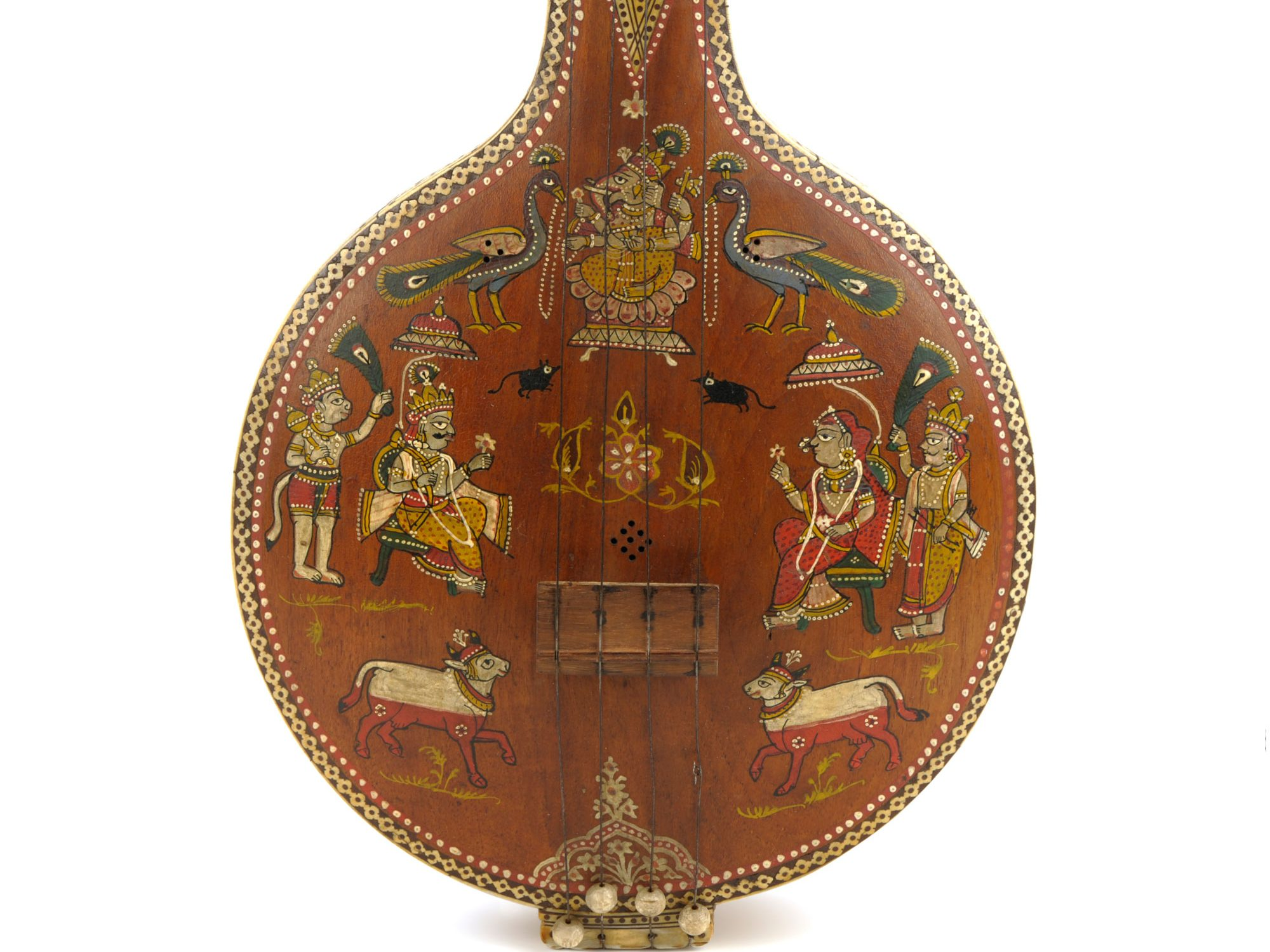 A close up of the base of a wooden stringed instrument. The base is round with lots of inlaid decorations showing people and birds around the strings