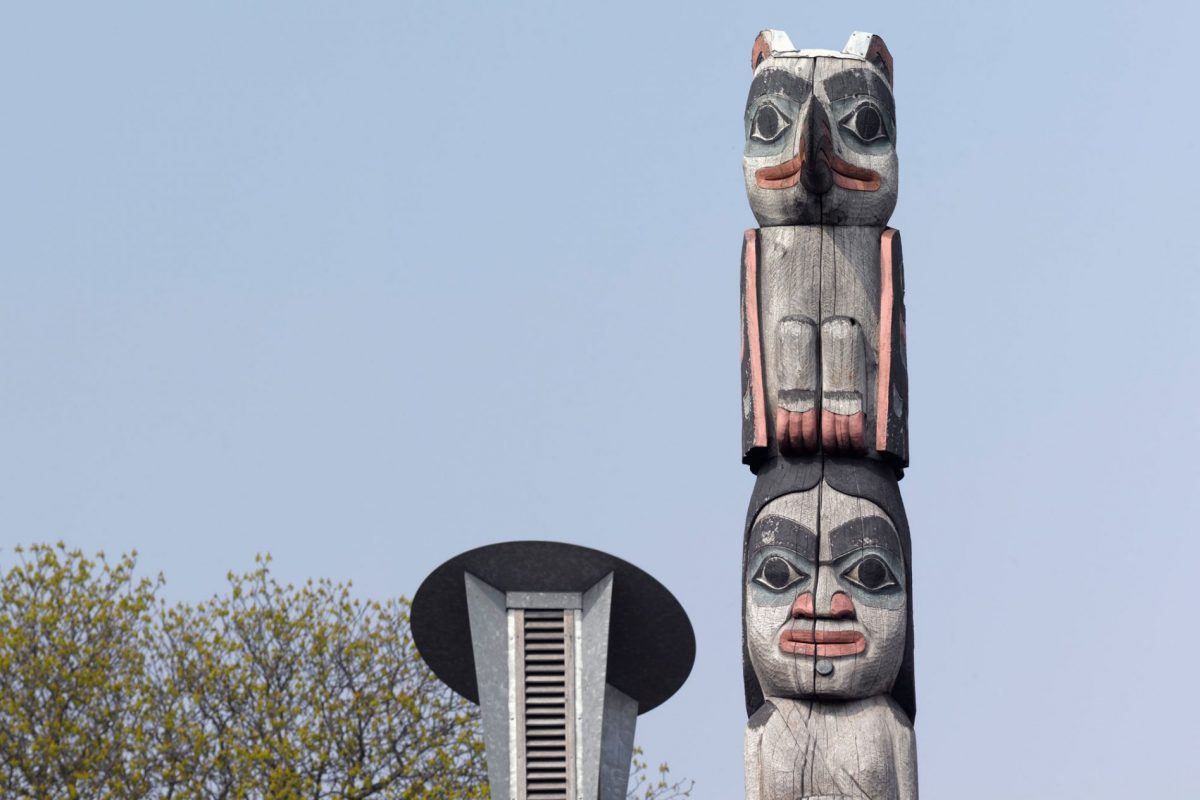 A totem pole made up of three figures. The first is a bear, the second is a woman and the third is a bird. Behind the pole is a building with grass growing on the roof and tall air vents.