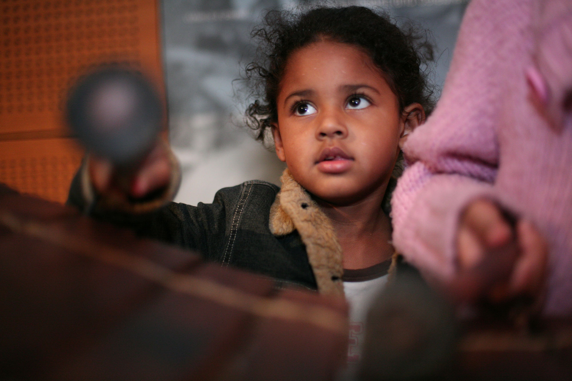 A young girl looks up as she holds a beater over a wooden instrument. Another child is just seen to the side