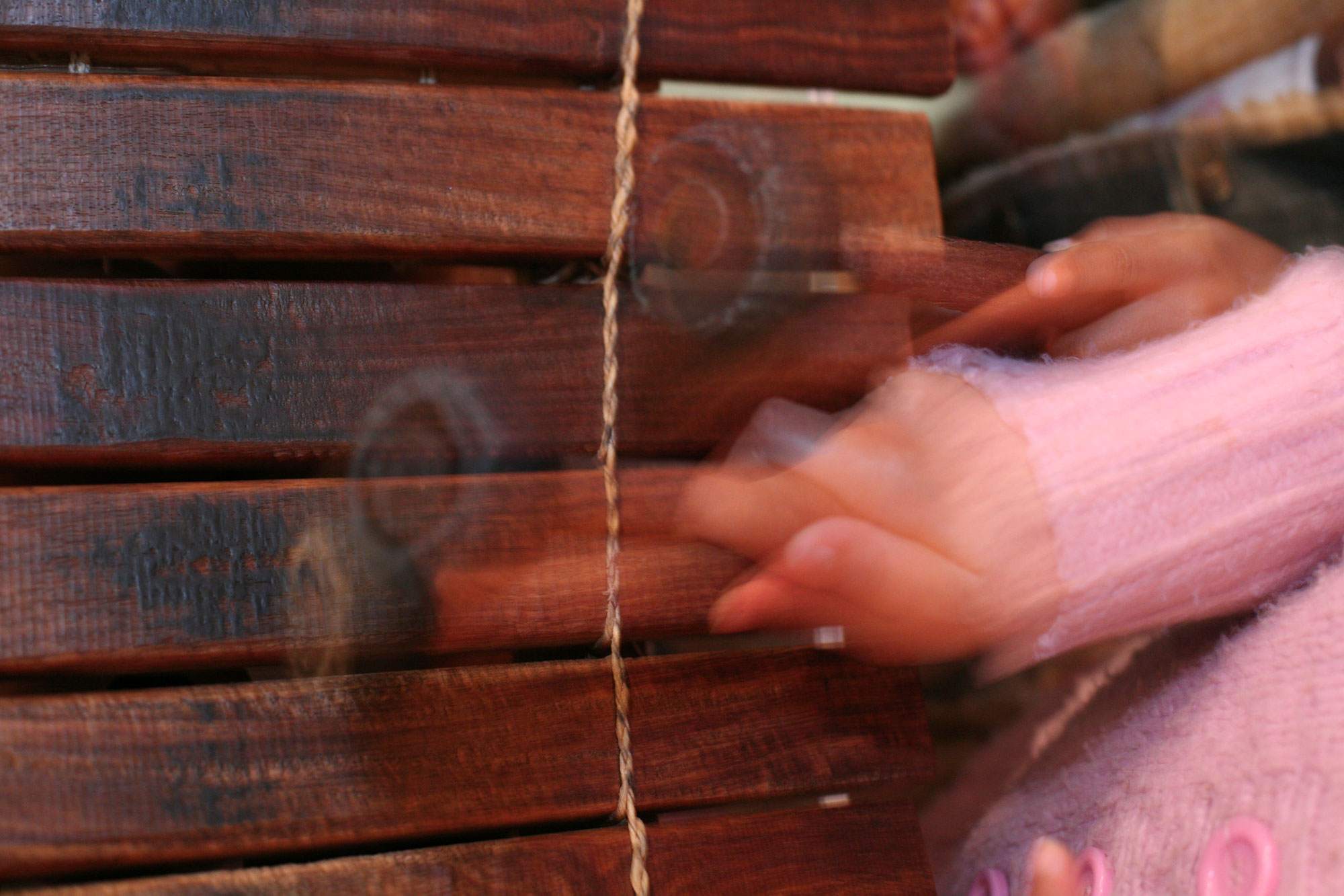 A child's hands are holding beaters to play a slatted wooden musical instrument. They are blurry, as if in rapid motion.