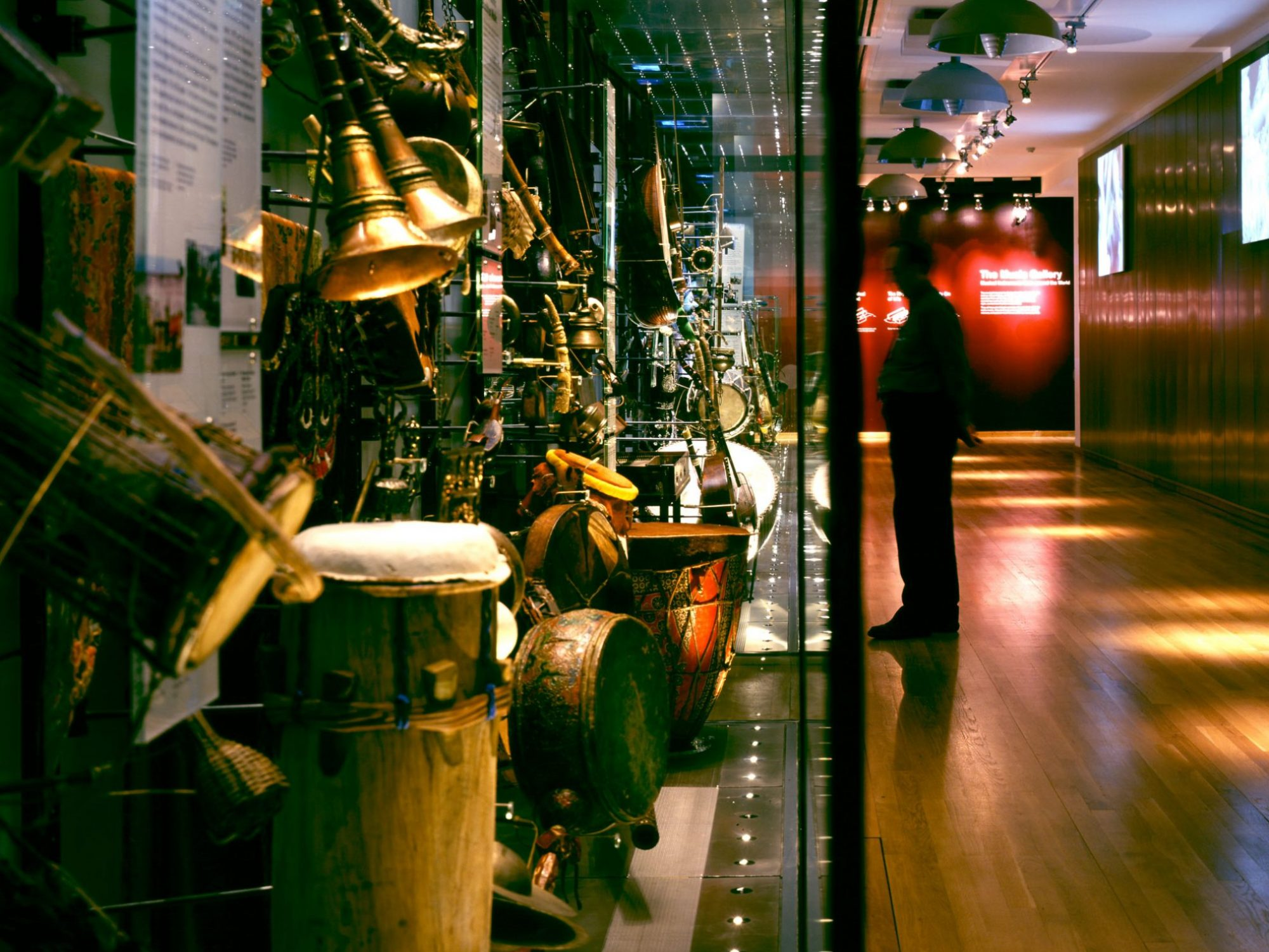 The shot shows the image divided into two. The left half of the image is the end of a display case full of intruments, and you can see drums and metal instruments. The right half is a stretch of gallery ending in a red wall. A man is standing in the distance, looking in at a case.