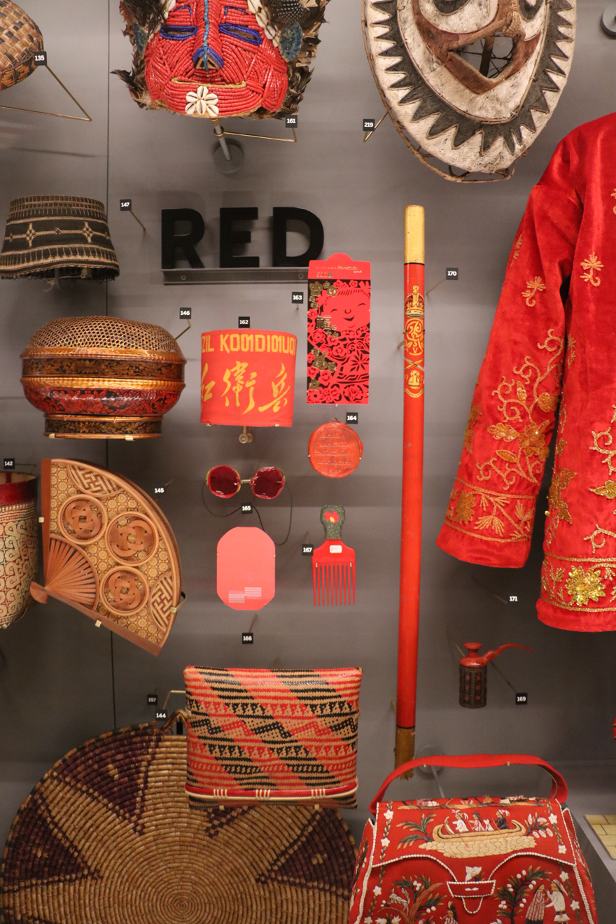 A group of different objects, all red, are clustered around a sign with the word red. Objects include a handbag, a jacket, a basket and a tin.