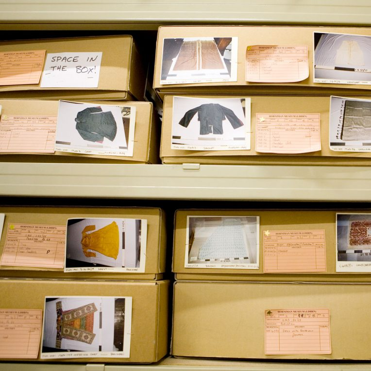 Two shelves with cardboard boxes on them. Each box has a number of images attaches which show their contents, and labels with details of the objects. All these objects look like clothes