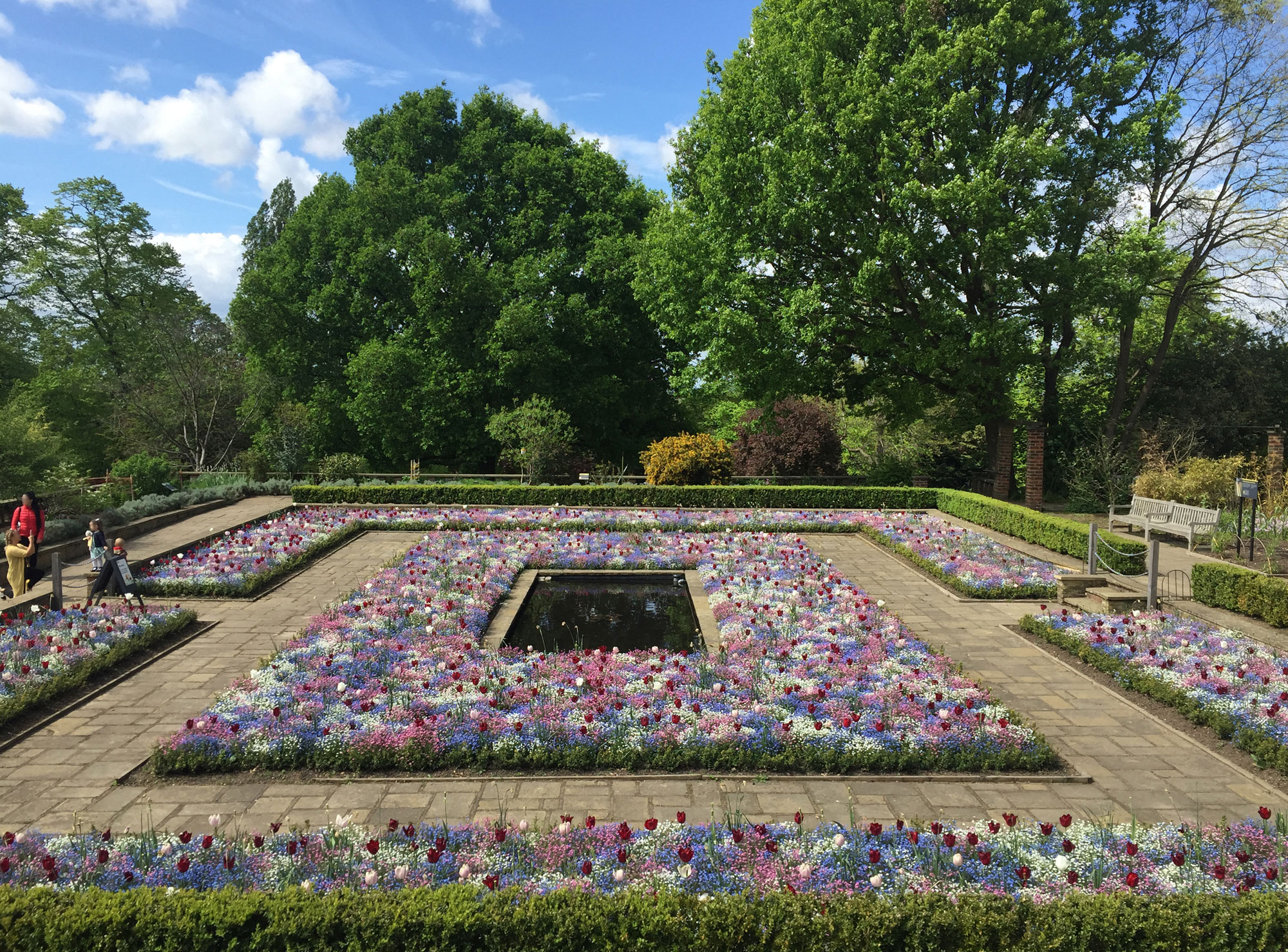A square pond sits at the centre of a square flower bed with a square path around it and more flower beds around that. The flower beds are full of colourful flowers in blues, pinks and whites. The area is lined with trees and the sky is blue.