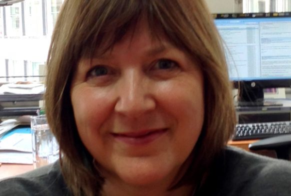 A woman sat in an office seen from the shoulders up, smiling at the camera