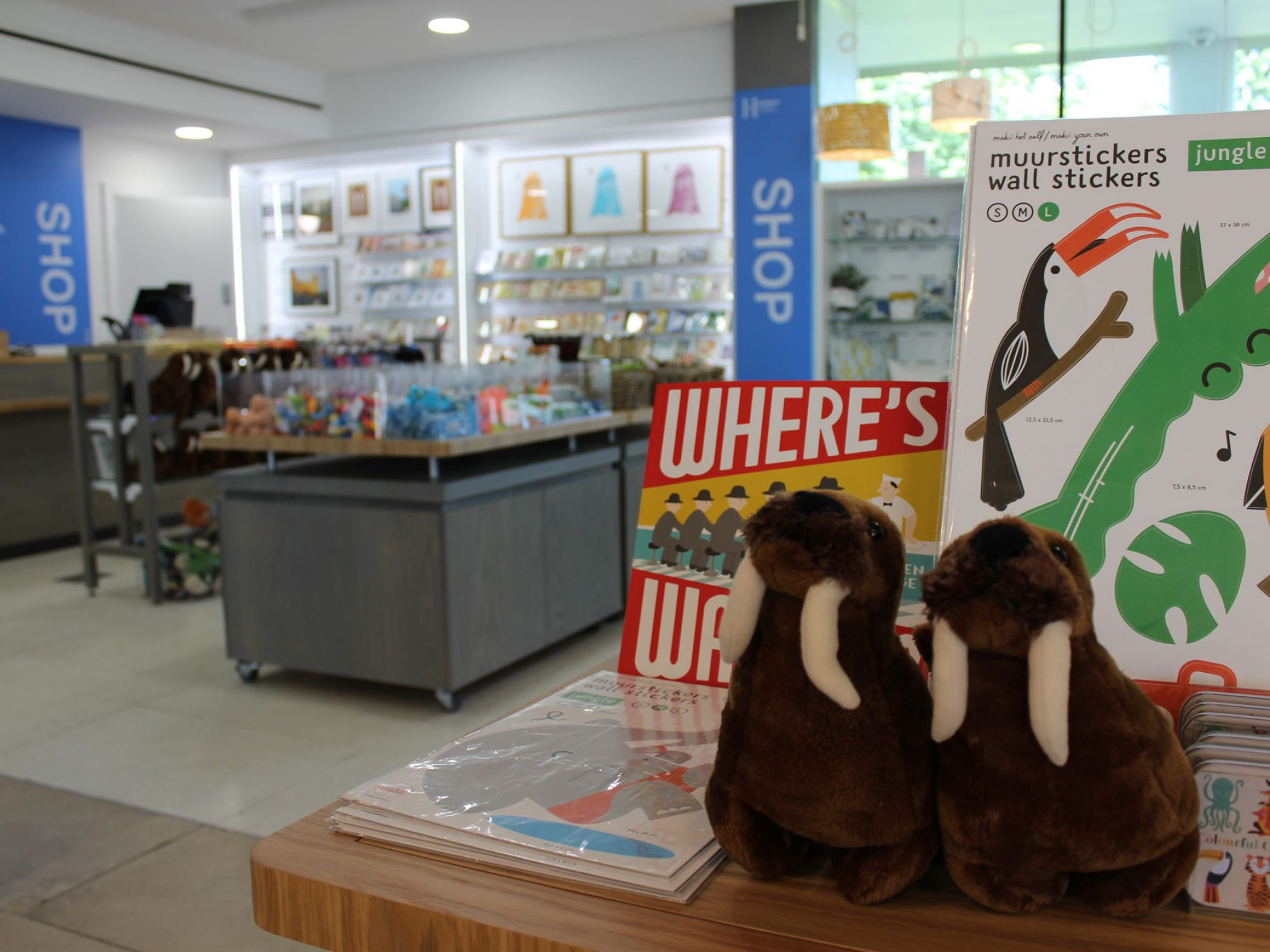 A shop display featuring two stuffed walrus toys, and some brightly coloured books are in the foreground. In the background is a shop with displays of cards, and tables with smaller goods on them.
