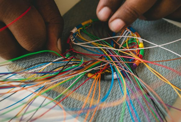 A pair of hands are weaving colourful thin wires around a circular base. Lots of the wires are sticking out in all directions