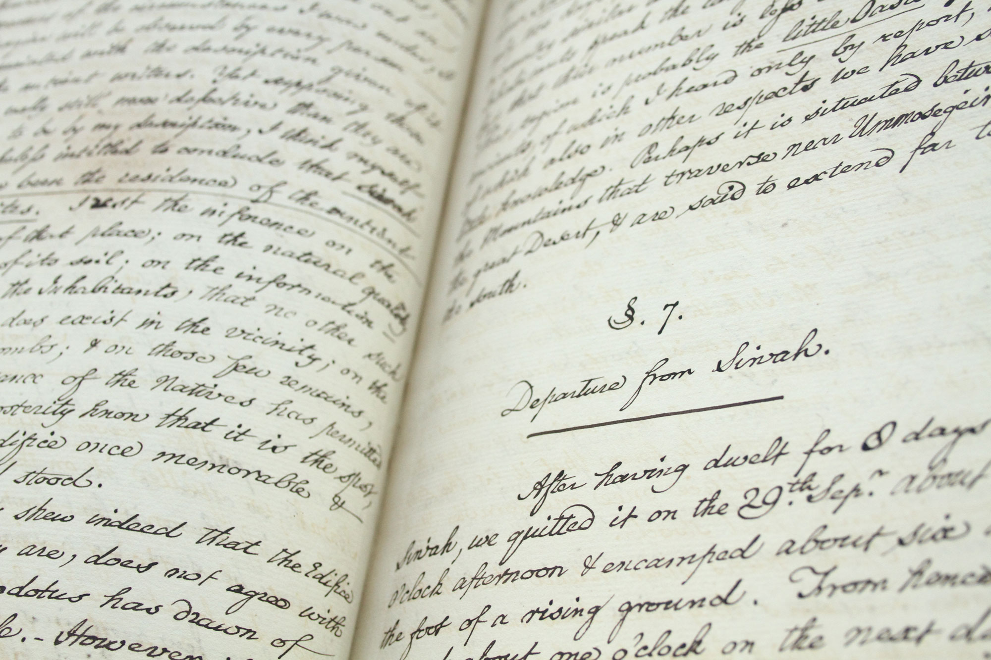 A close up of two pages of text written in pen - the words are impossible to read but the book looks old.