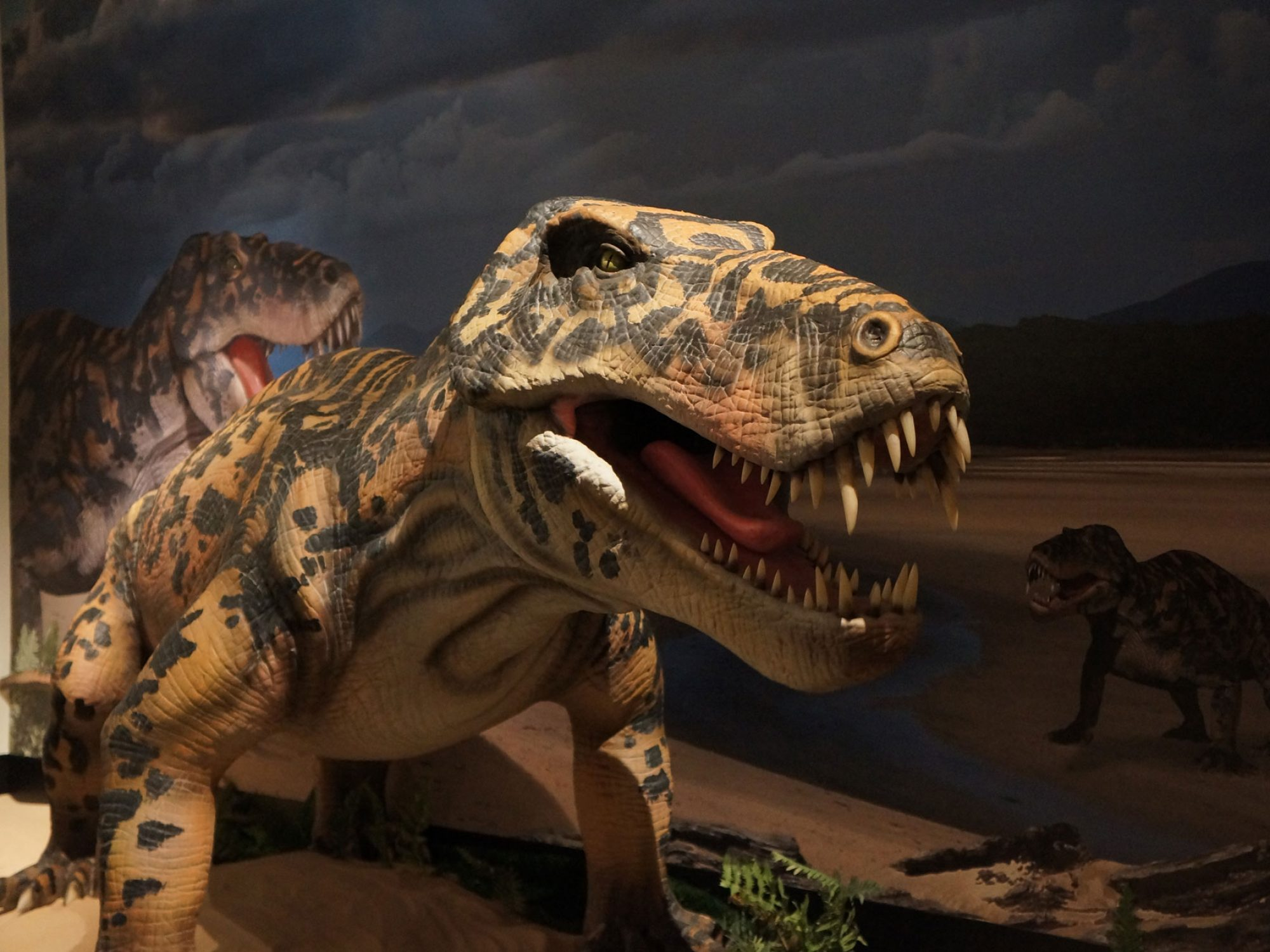 A model of a large toothy creature is posed with its mouth open and a picture of its habitat in the background