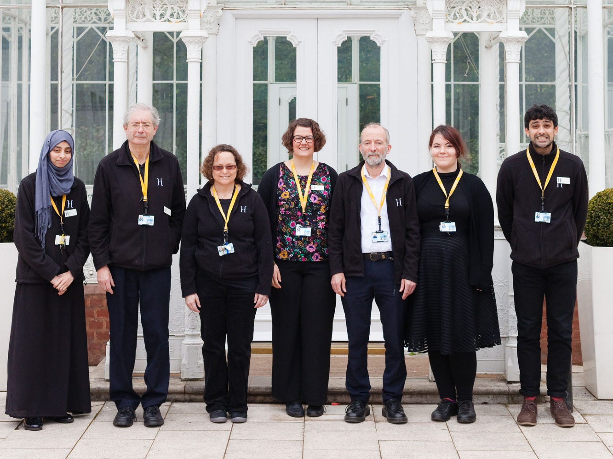 A line of people wearing mainly black outfits with yellow lanyards around their necks stand in front of a white glass house