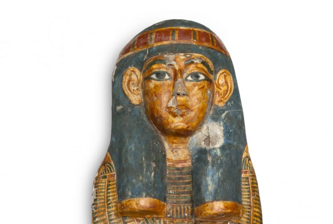 coffin in the shape of a human with symbols across the lid.