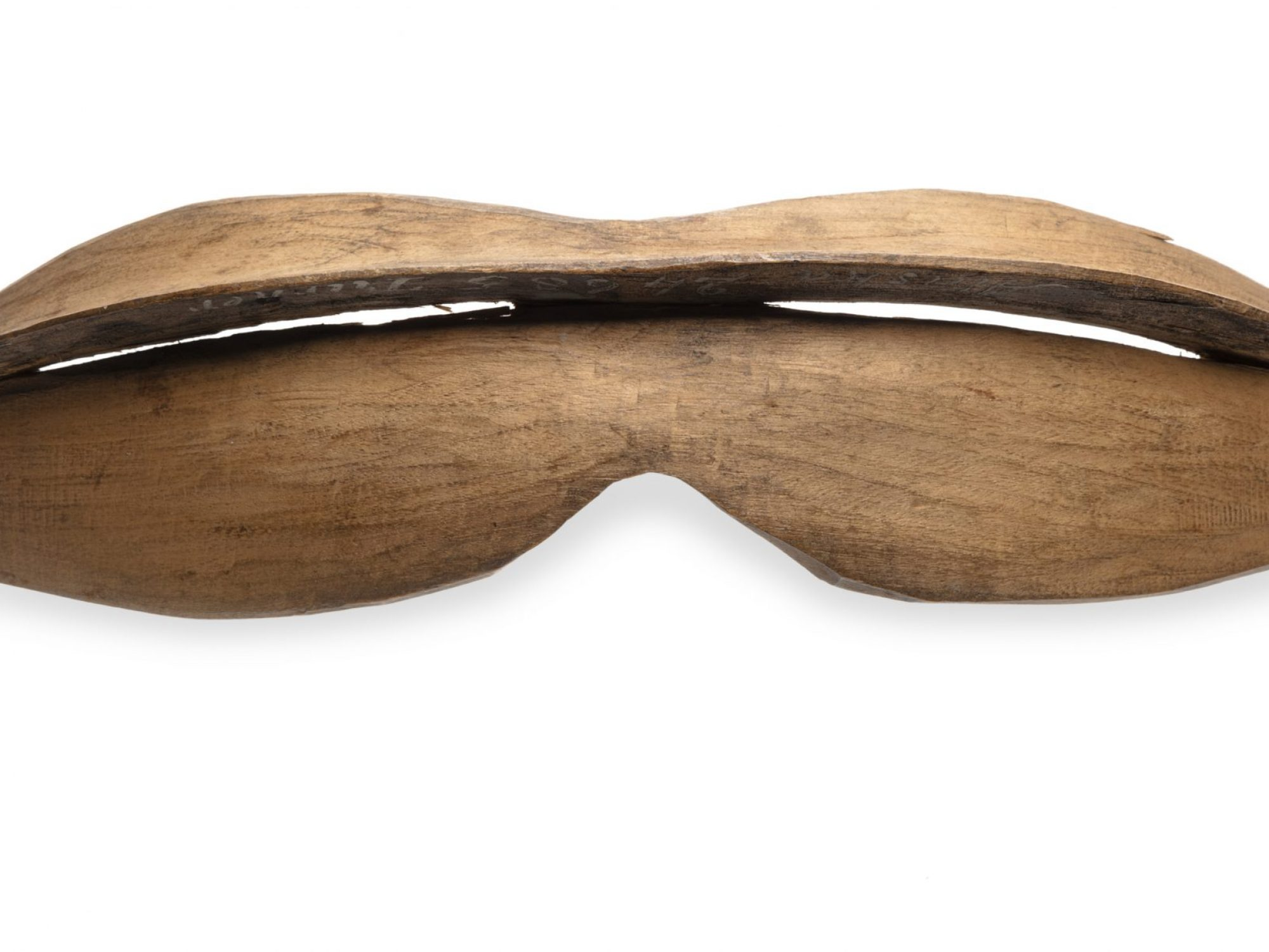 Wooden snow googles, shaped like bean pod with slit in middle for visibility