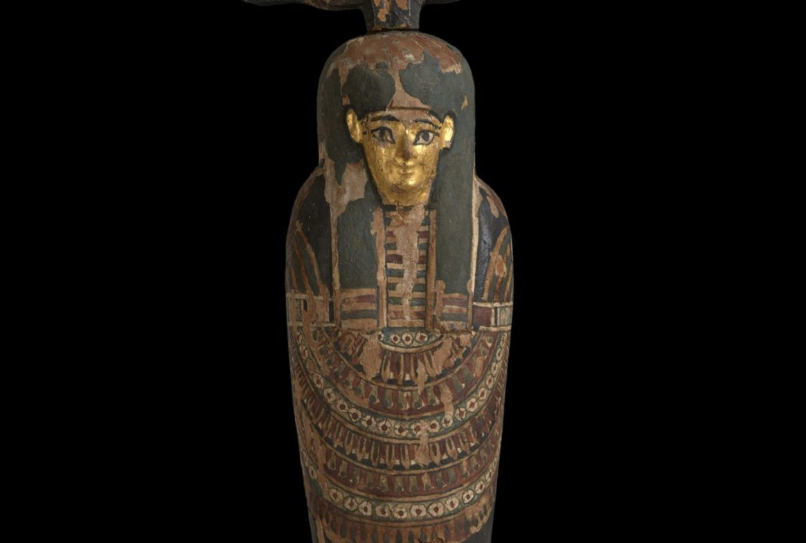 Figurine of Egyptian person with long curved headress type item on head.