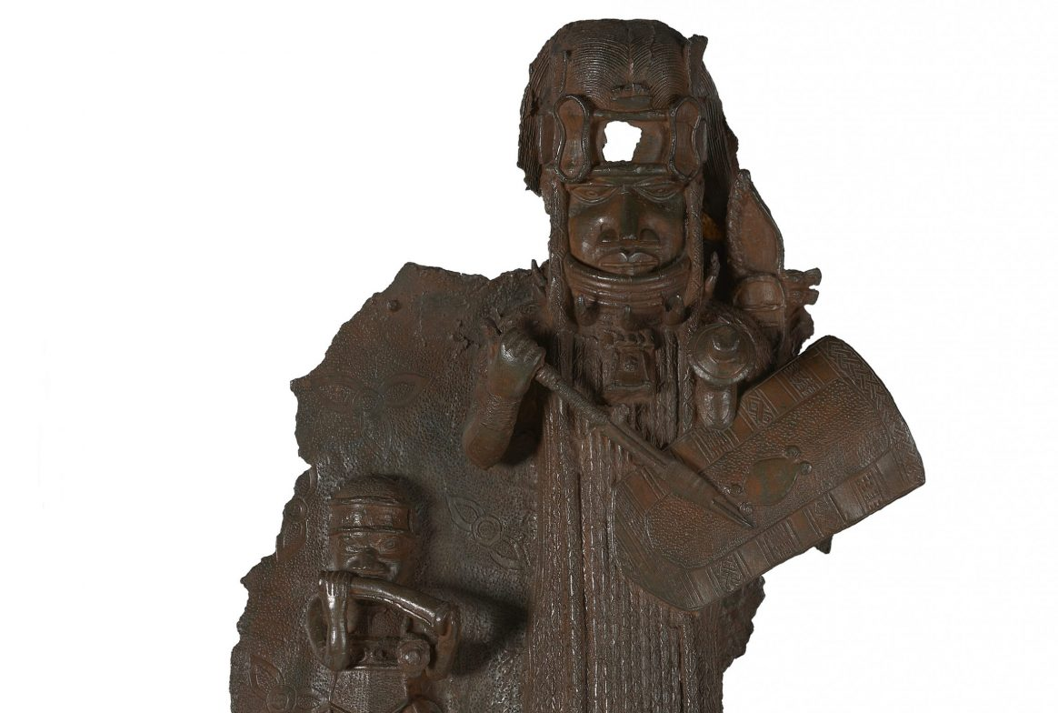 Bronze plaque of person in warrior gear and smaller person with tool