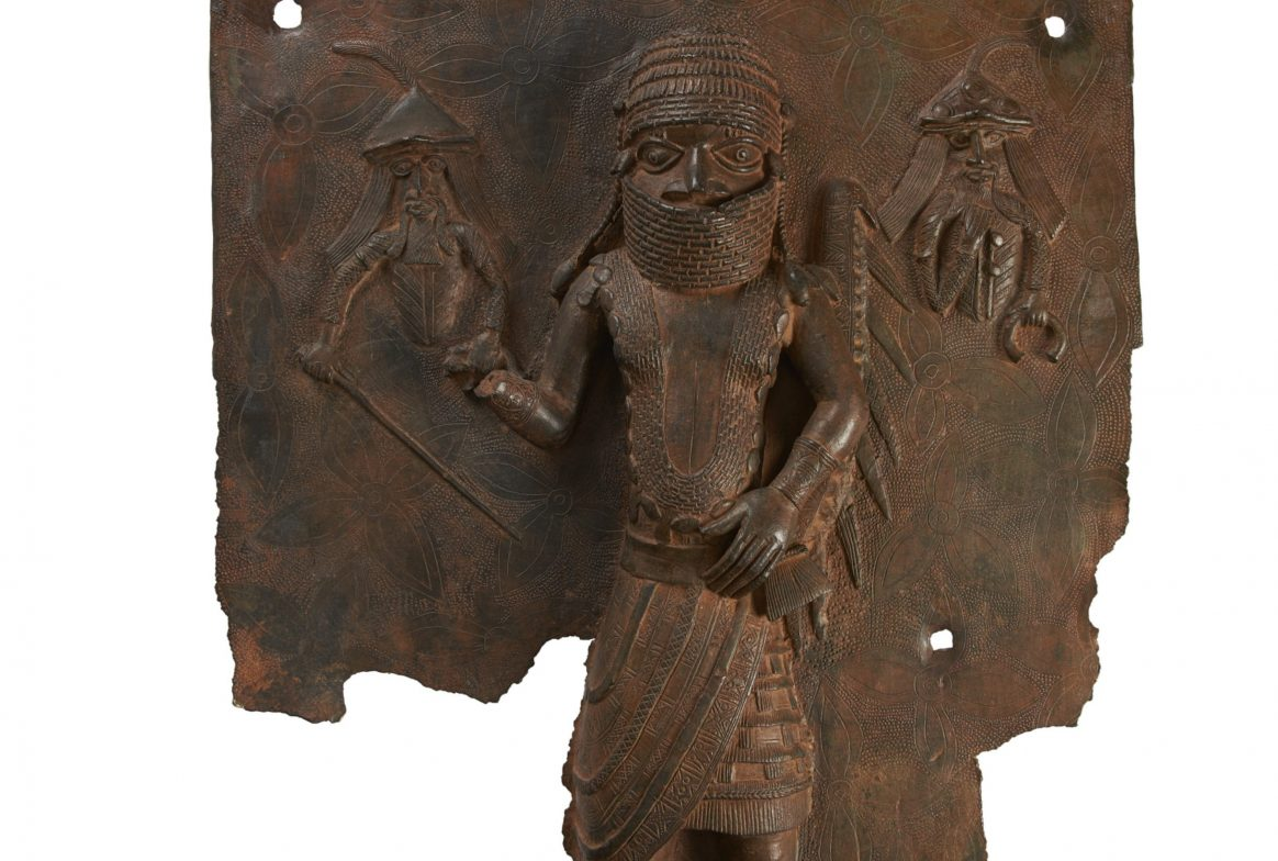 Bronze plaque of person with two people in hats behind him at either side.