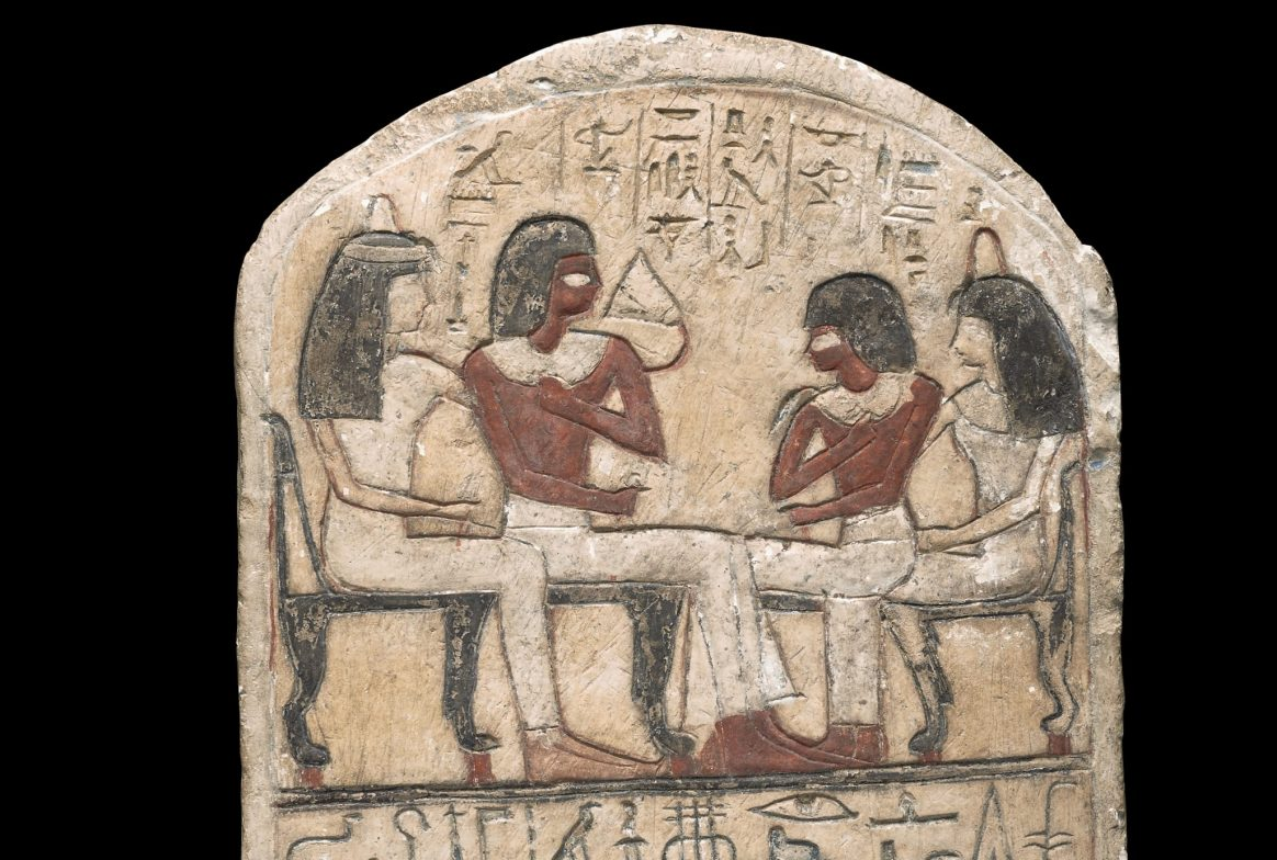 A cream slab with 4 people engraved into it and Egyptian symbols