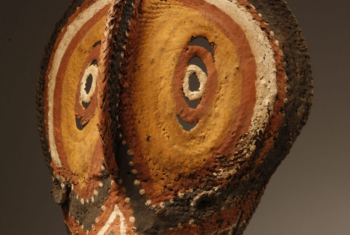 Brown mask carved from a yam vegetable. It has two large circular eyes, and protruding nose running from the top of the head to under the eyes, and a mouth which looks like a spout. It is unclear how this could be worn, but could be a full head mask.