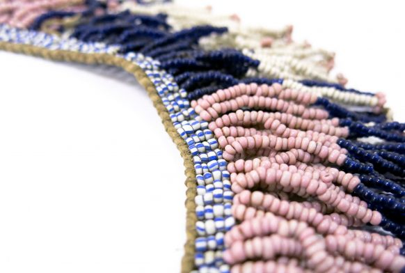 A rope of beads, white, pink and blue, strung together in a neck piece. They are seen in close up against a white backdrop