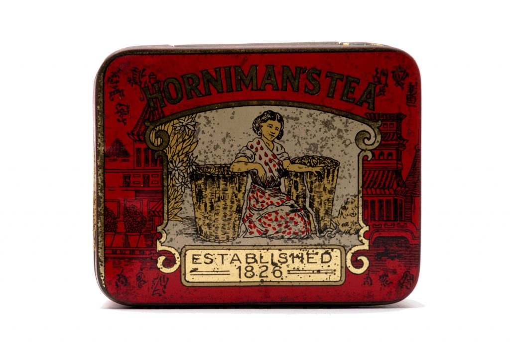 An old mottled tea tin with the words Hornimans Tea on it and a picture of a woman. The tin is red and gold.
