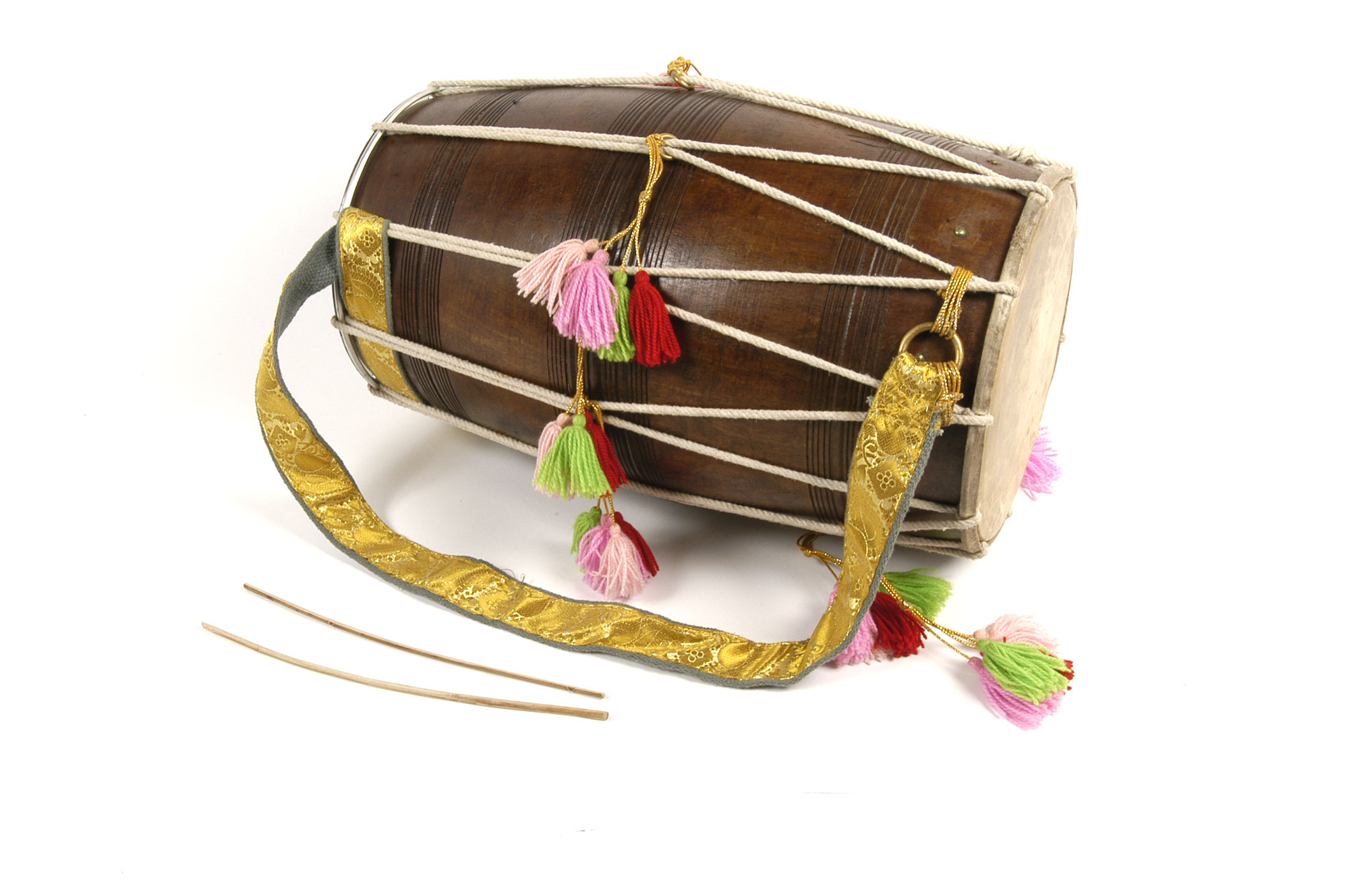 A round long drum, with a yellow strap so that it can be carried across the body and bit with two beaters without dropping it. There are pom poms on each side