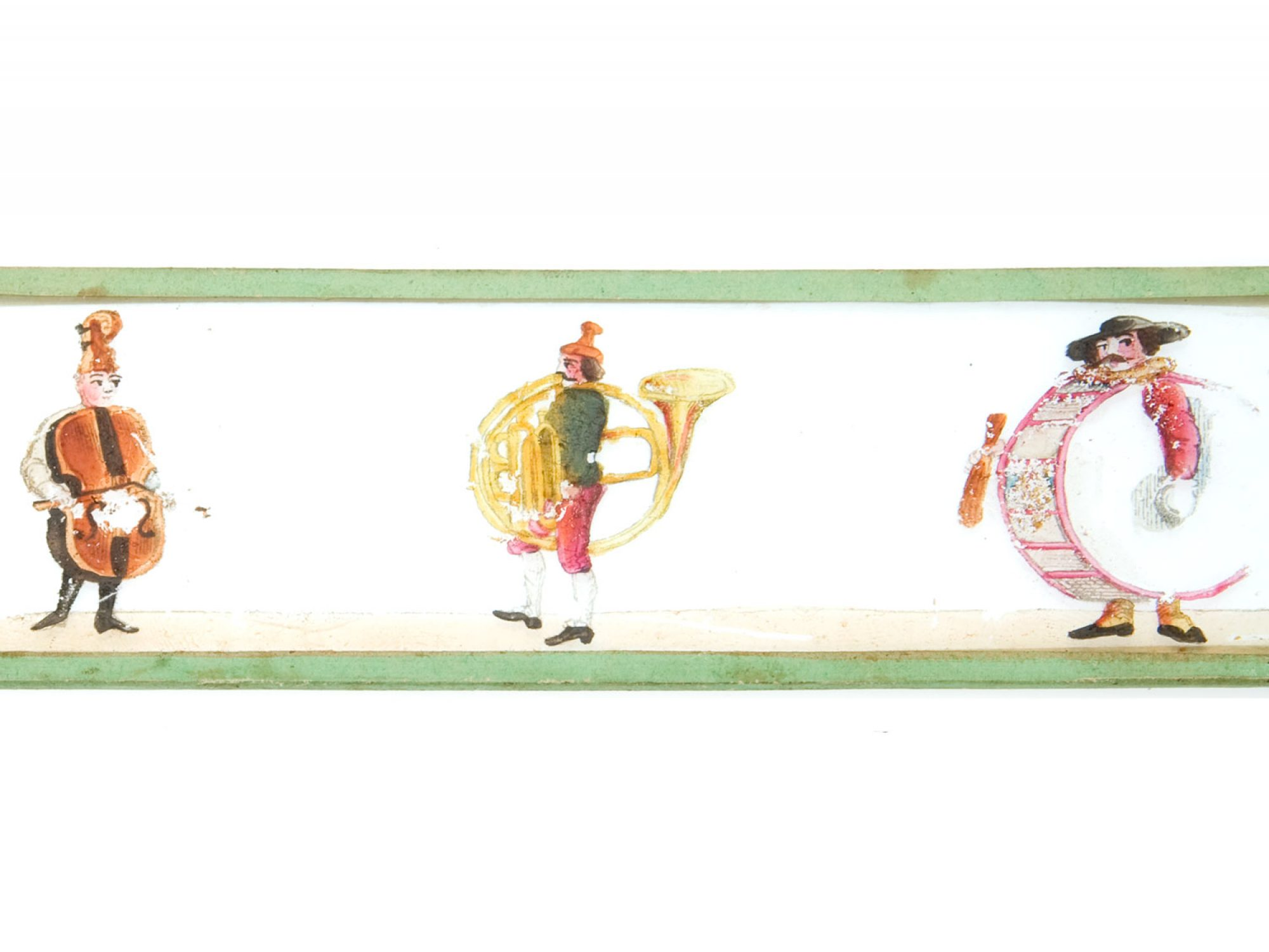 A glass slide edges in green wood. On the glass slide are three figures painted, all wearing life sized musical instrument costumes like a drum and a cello and a horn.