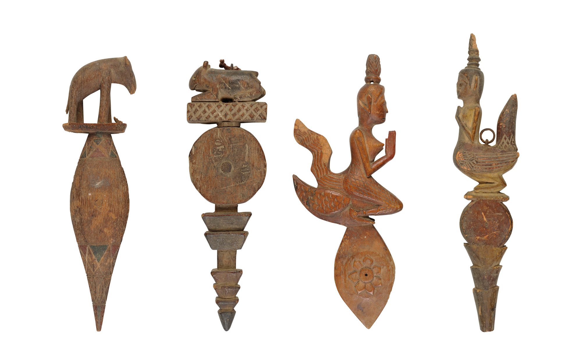 Wooden figures carved into different shapes. There are four and all have a circular, spoon like quality to them