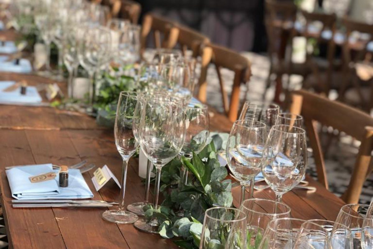 A table set for a party with place settings of different glasses, silverware and napkins with names on them