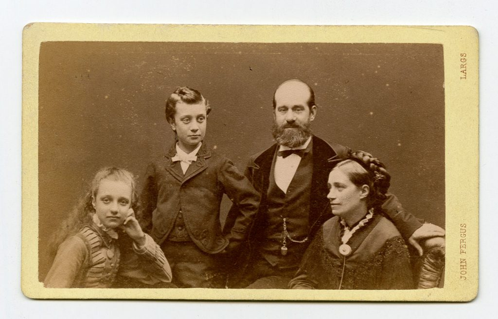 A black and white family portrait with the figures seated, apart from the boy. Left to right is a girl with her head on her hand, a boy with his hand to his hip, a bearded man looking at the camera and a woman looking towards the girl.