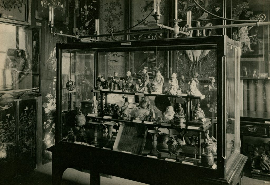 A black and white photograph showing a room filled with images on the walls. A large case is central to the room with many small figures behind glass.