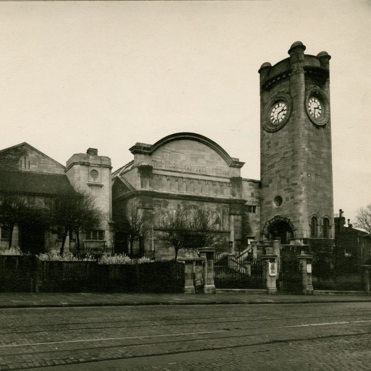 A black and white dated photograph of the outside of the Horniman Museum and Gardens. A clocktower stands to the right with a curved building next to it in the middle and a shorter building with two small turrets to the left. Trees and shrubs are along the front and in front of those is a road.