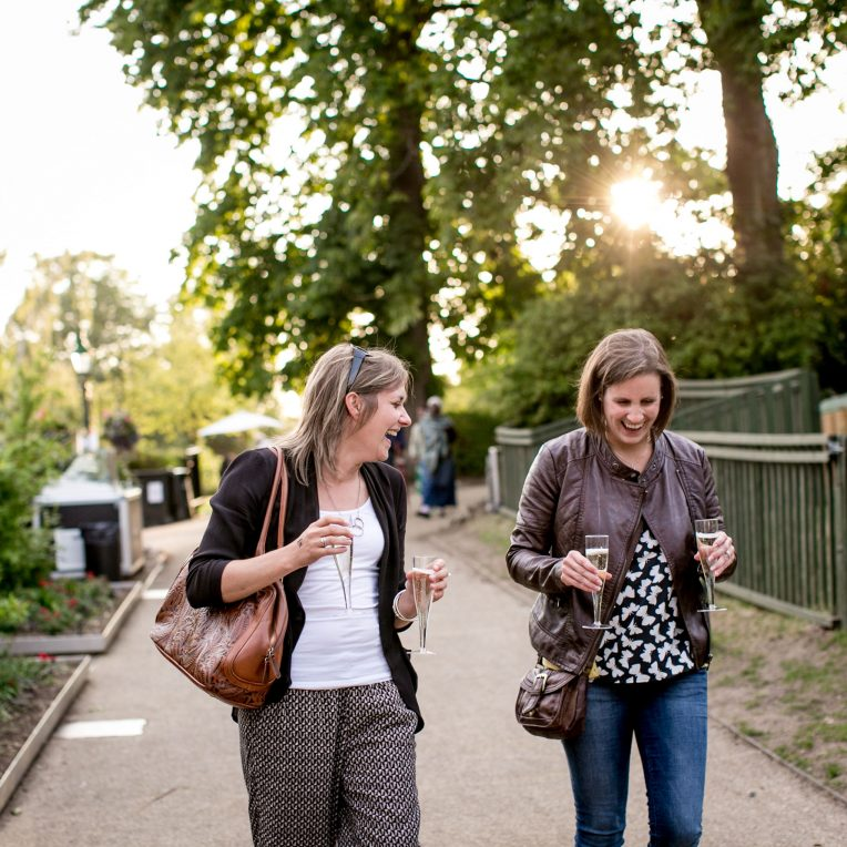 Two women walk up a garden path as the sun is going down, holding glasses of wine in their hands, talking and smiling